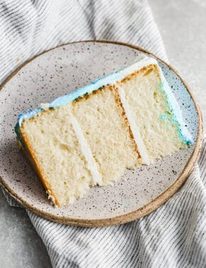 A slice of smash cake, vanilla cake, on a plate.