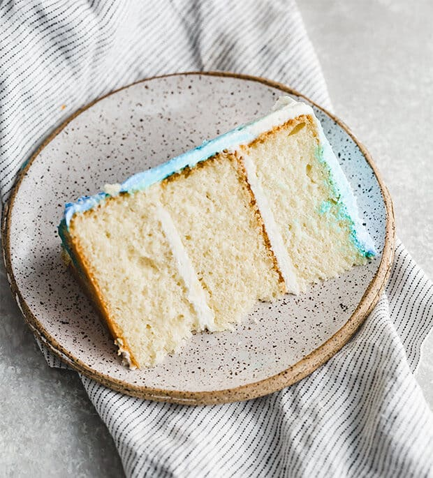 A slice of smash cake, vanilla cake, on a plate.