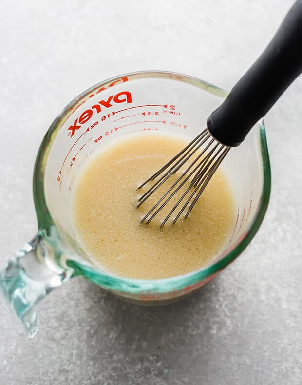 A glass measuring cup with the wet ingredients whisked together.