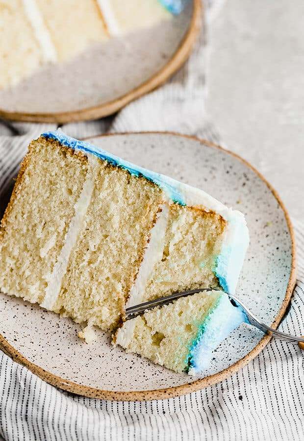 A slice of vanilla cake, with blue frosting for a smash cake.