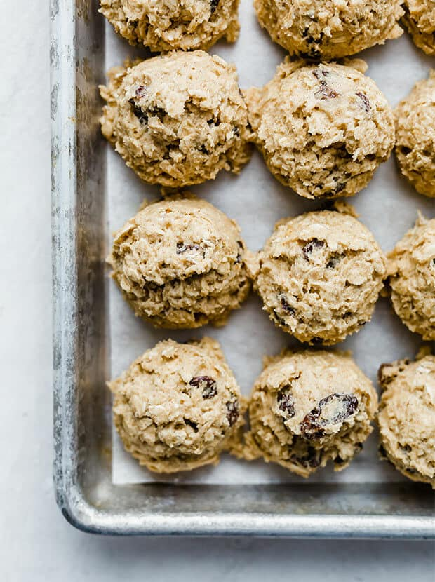 Oatmeal raisin cookie dough balls lined next to each other on a baking sheet.
