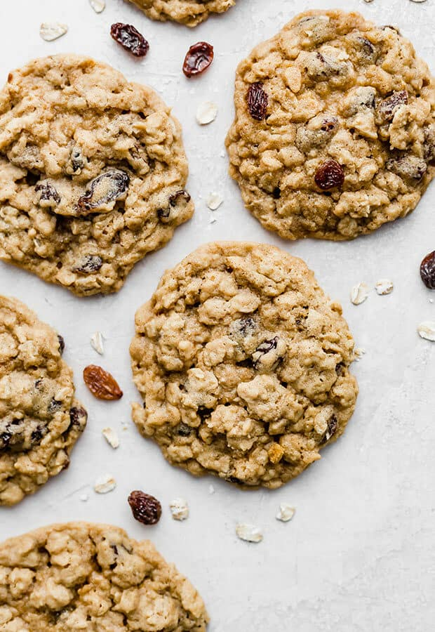A Soft Oatmeal Raisin Cookie surrounded by oats and raisins.