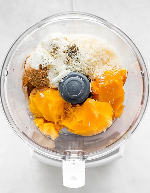 A food processor with butternut squash ravioli filling ingredients.