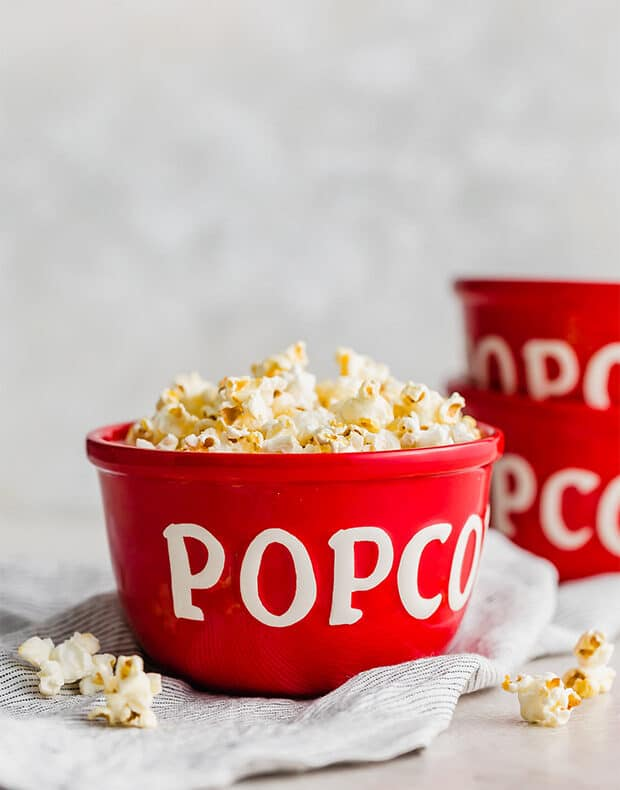 Red popcorn bowls full of homemade movie theater popcorn.