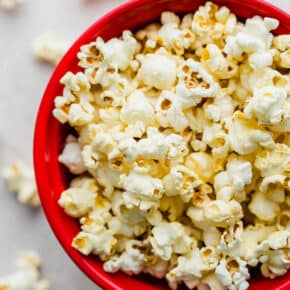 A close up photo of movie theater popcorn in a red bowl.