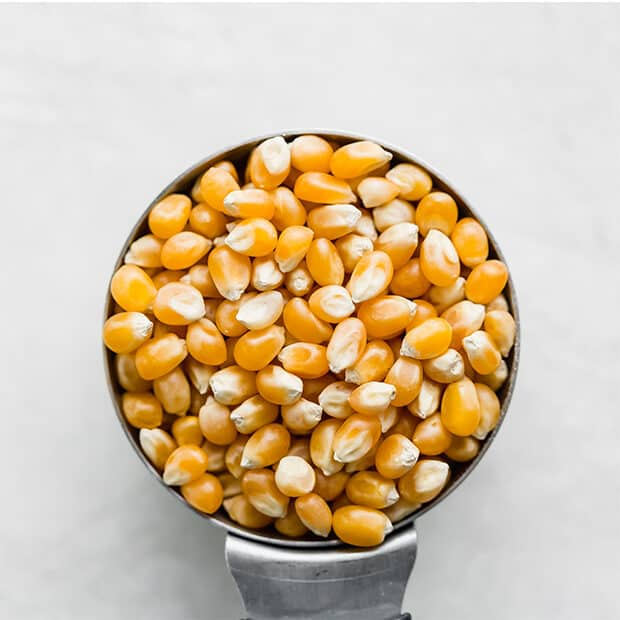A metal measuring cup full of popcorn kernels.