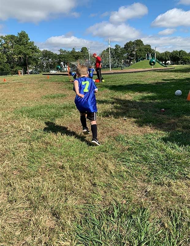 A boy in a soccer jersey running.