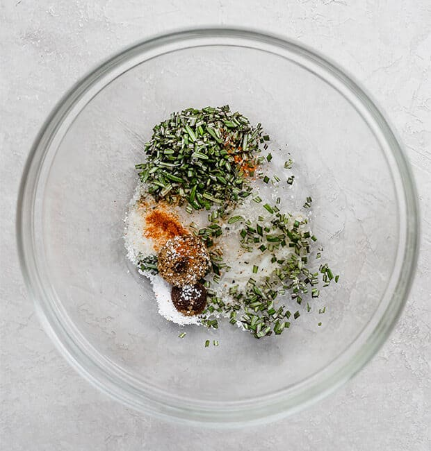 A glass bowl with fresh rosemary, cayenne, salt, and melted butter.