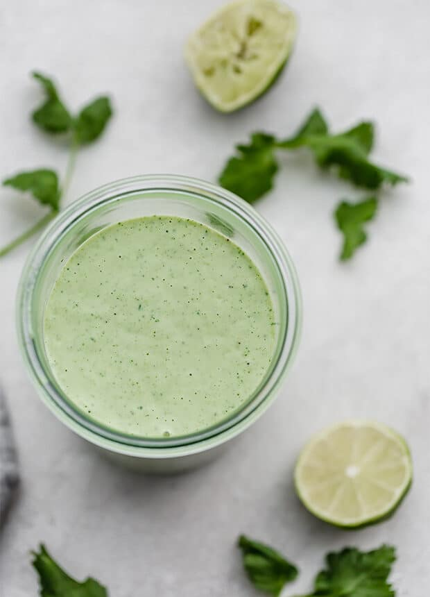A photo of cilantro lime dressing surrounded by cilantro and lime slices.