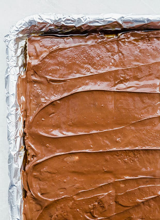 A close up photo of melted chocolate overtop Christmas Crack.