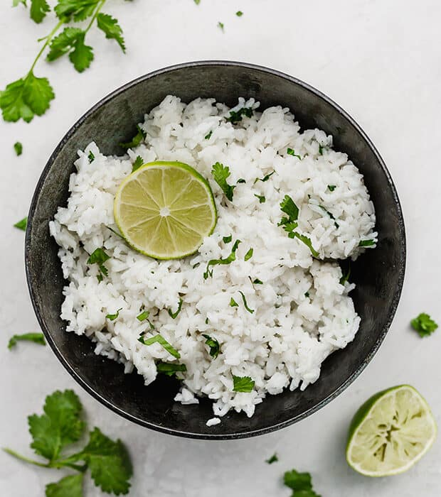 A bowl of Cilantro Lime Rice with half of a lime in the bowl for garnish.