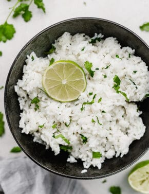 A bowl of Cilantro Lime Rice with a lime wedge on top.