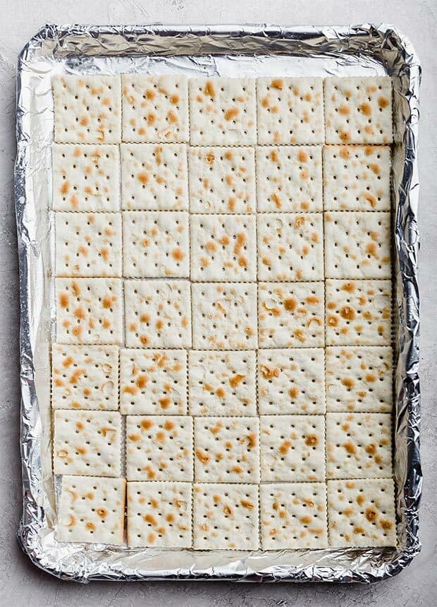 A jelly roll pans lined with tin foil and saltine crackers for making Christmas Crack.
