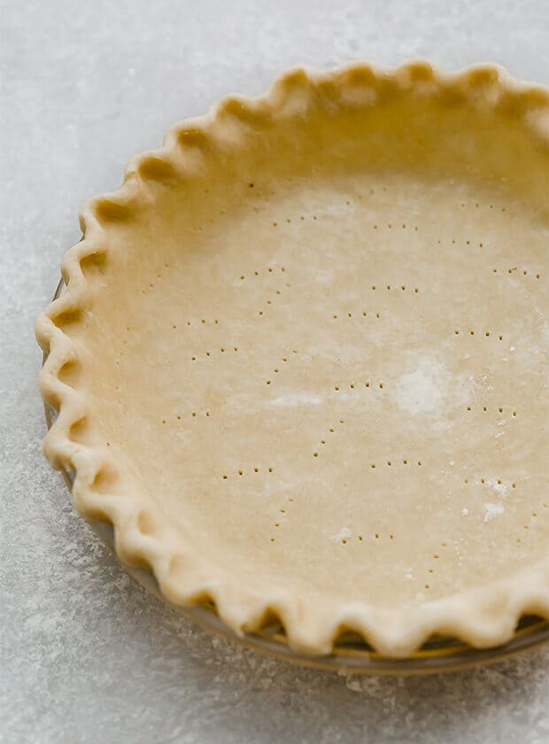 A fluted pie crust in a pie pan.