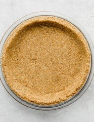 An overhead photo of a pie plate filled with a graham cracker crust recipe.
