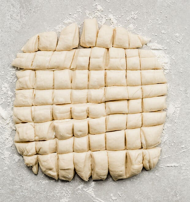Monkey bread dough cut into 64 small squares.