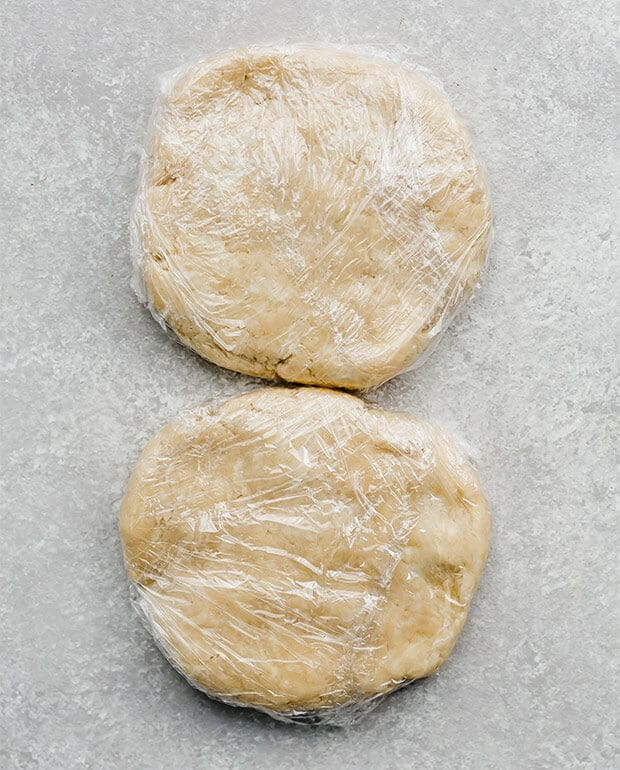 Two pie crust disks wrapped in plastic wrap.