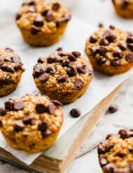 Chocolate chip topped pumpkin baked oatmeal cups sitting atop a closed book.