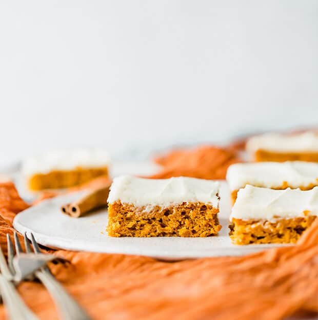 Slice of pumpkin bar topped with cream cheese frosting.