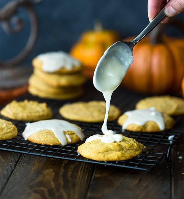 Glaze drizzling over pumpkin cookies.