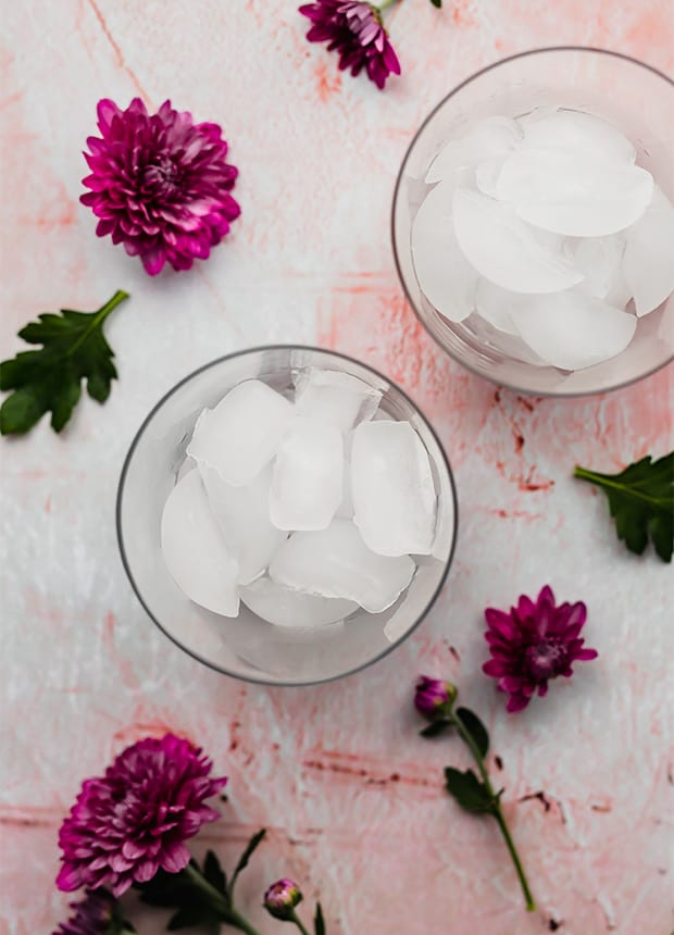 An overhead photo of a glass cup full of ice cubes.