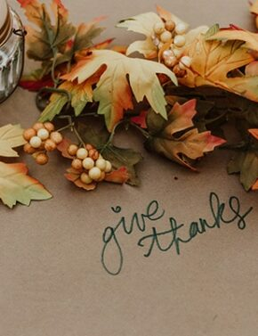 "Leaves on a table with ""give thanks""written on the tablecloth."