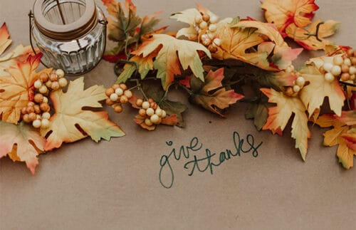 """Leaves on a table with """"give thanks""""written on the tablecloth."""