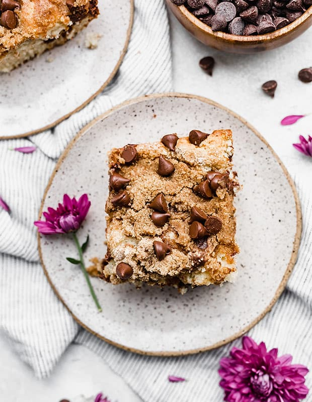 A slice of Chocolate Chip Coffee Cake with a purple flower next to the cake.