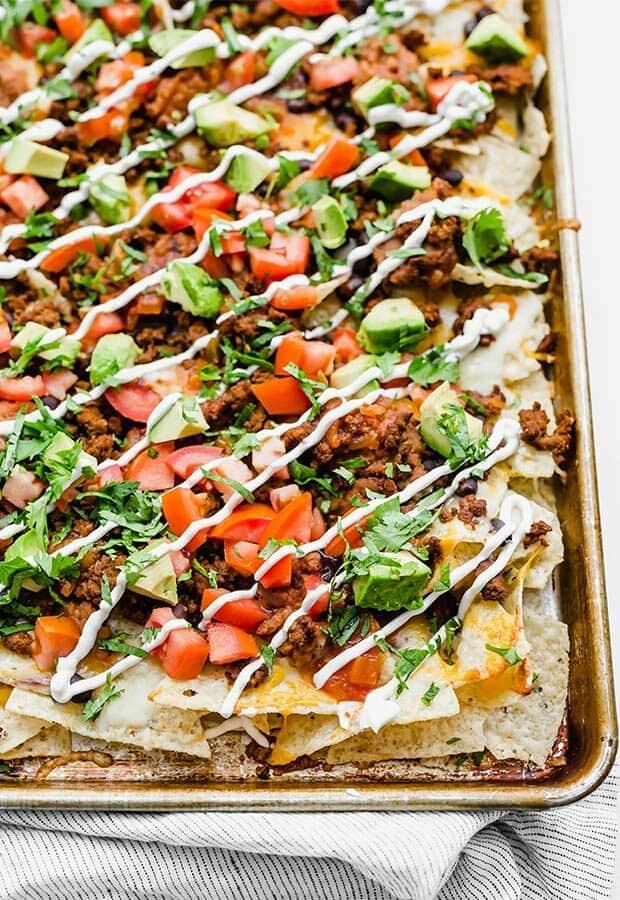 Loaded nachos on a baking sheet.