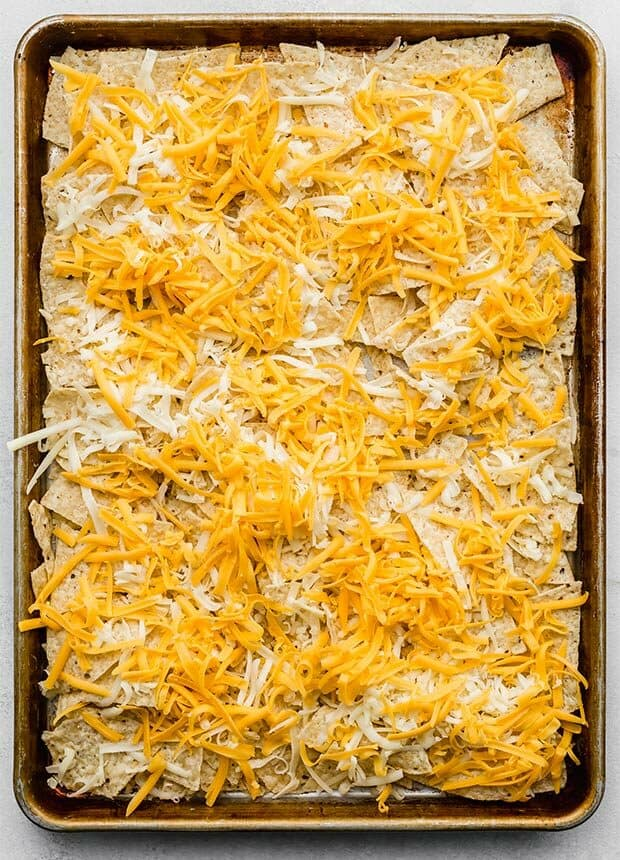A baking sheet covered in tortilla chips and shredded cheese.