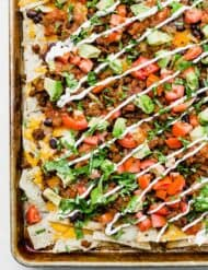 A baking sheet full of loaded nachos.