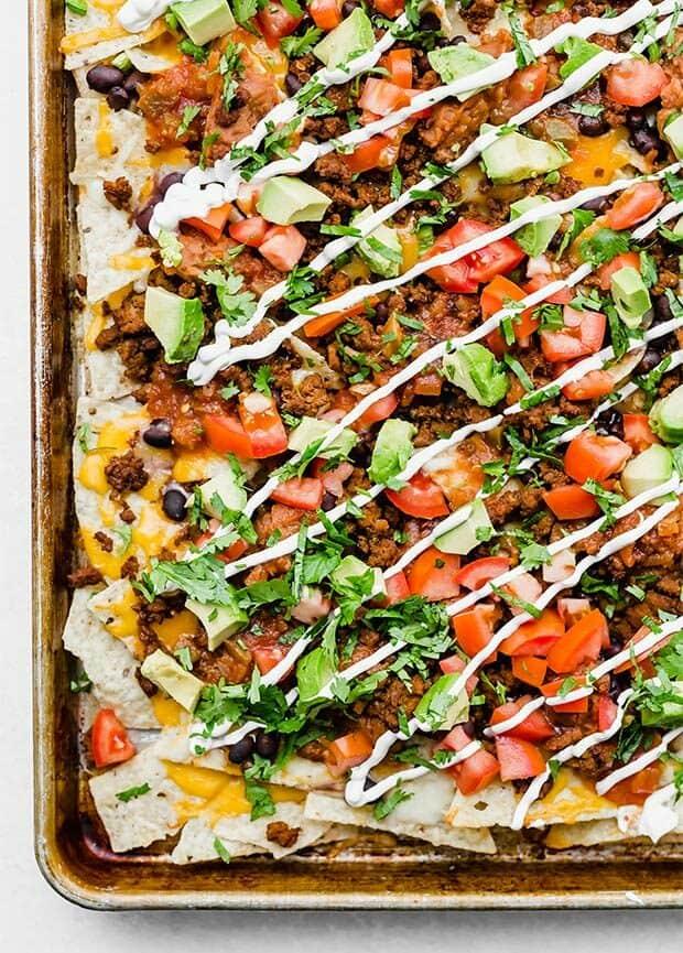 A baking sheet full of loaded nachos.