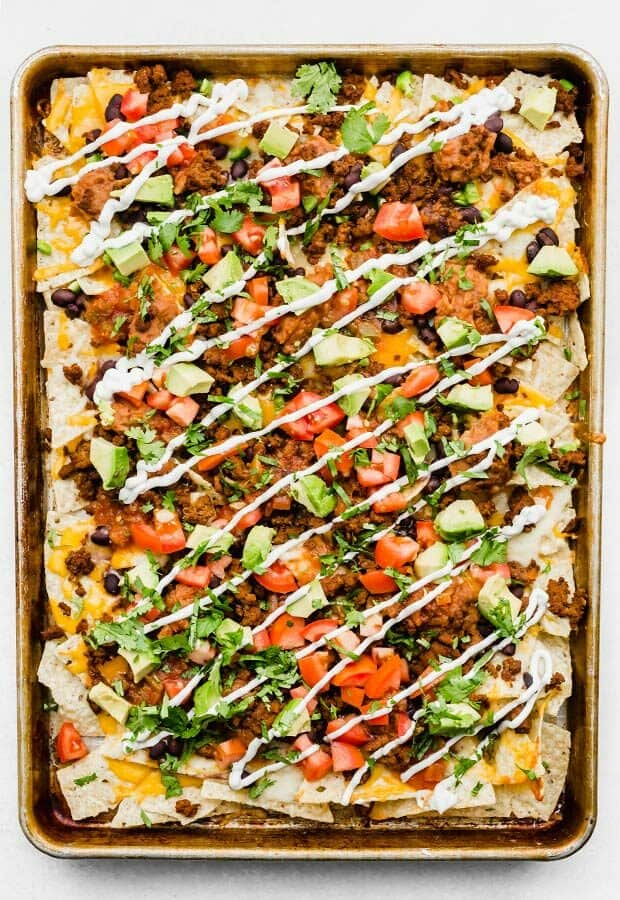 An overhead photo of a baking sheet full of loaded nachos, garnished with cilantro and sour cream.