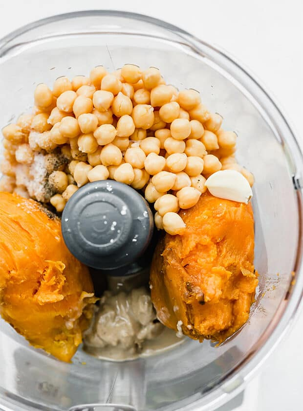 A food processor with the ingredients for making Sweet Potato Hummus.