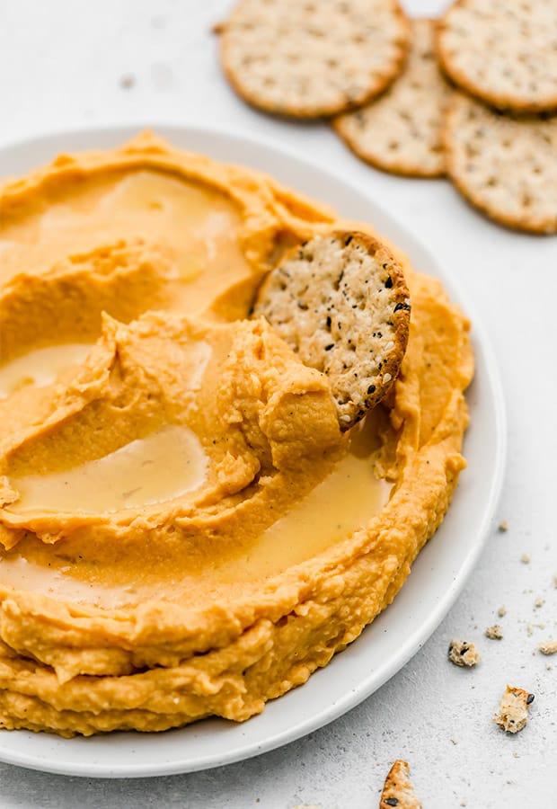 A cracker being dipped into fresh homemade sweet potato hummus.