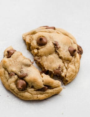A homemade Crumbl chocolate chip cookie being torn in half.