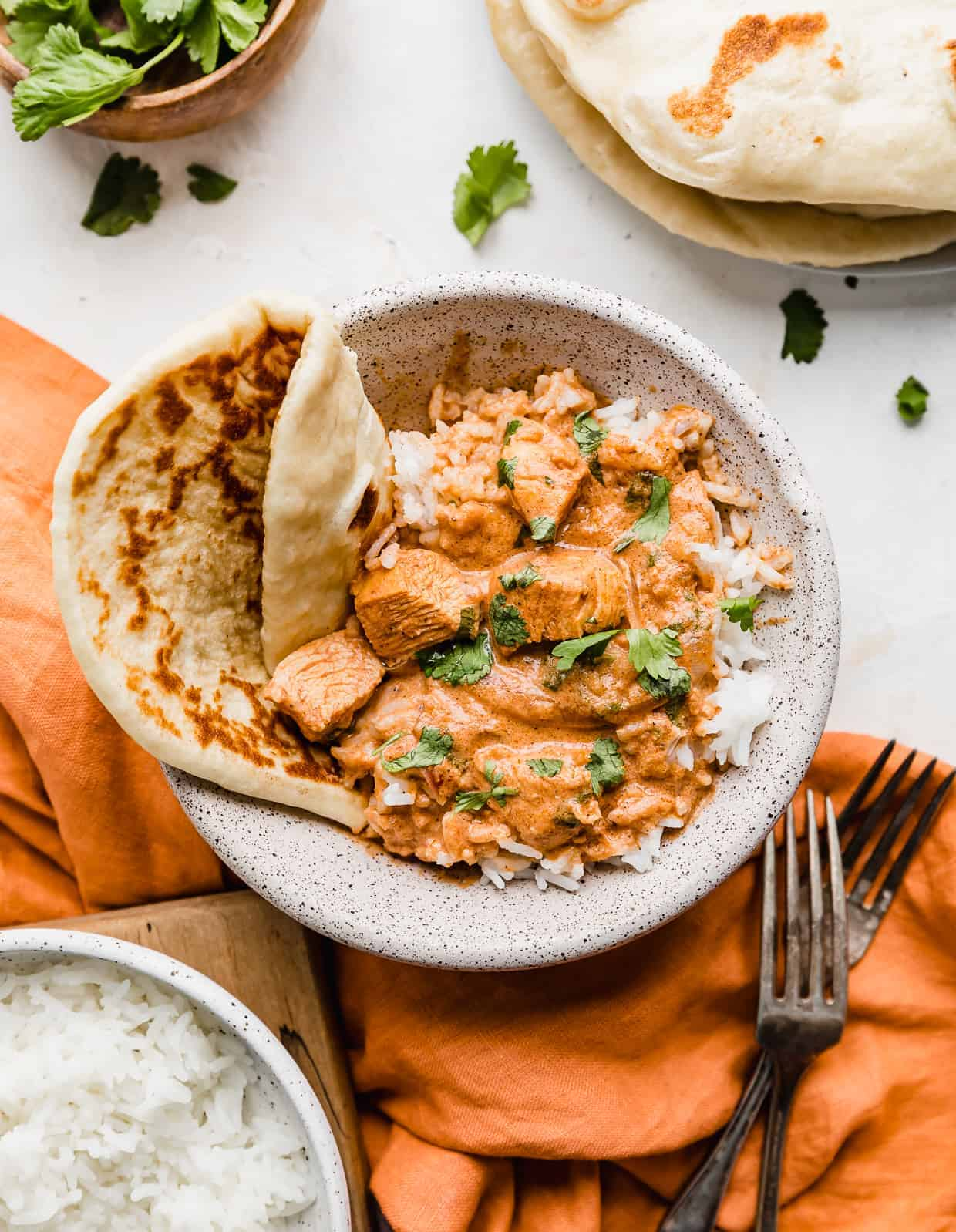 A bowl with Indian Butter Chicken in it, with a side of naan bread and rice.