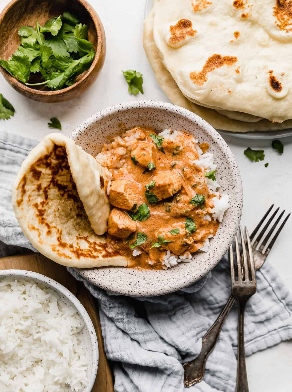 A bowl of Indian Butter Chicken Recipe surrounded by naan bread and cilantro.