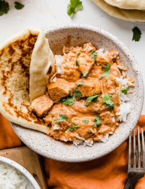 A bowl of Indian Butter Chicken overtop of white rice and garnished with cilantro.