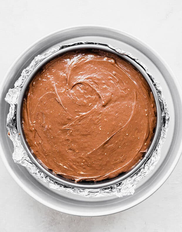 Nutella Cheesecake in a springform pan sitting in a larger circle pan.