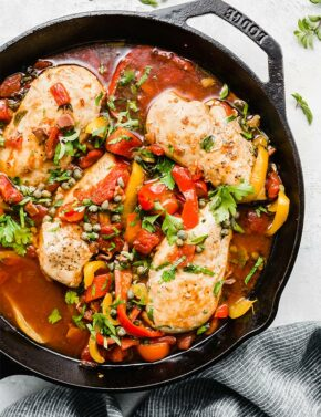 A cast iron skillet with cooked roman chicken topped with sliced peppers and capers.