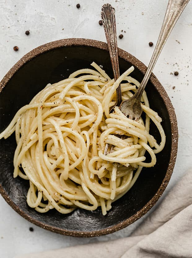A fork and spoon twirling bucatini Cacio e Pepe pasta.