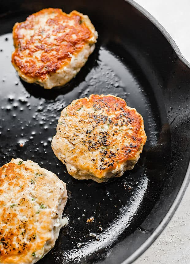 A cast iron skillet with browned salmon burgers cooking.