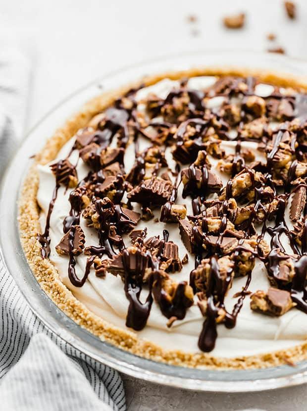A no-bake peanut butter pie topped with chopped Reese's peanut butter cups.