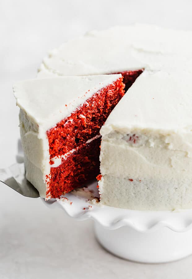 A slice of red velvet cake being cut out of a cake.