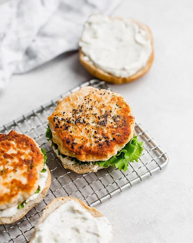 A cooked salmon burger on a hamburger bun.