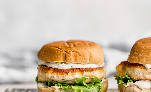 Salmon burgers on a bun with lemon dill mayo and lettuce.