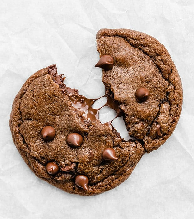 A Nutella cookie being torn in half, with melty Nutella spilling out.