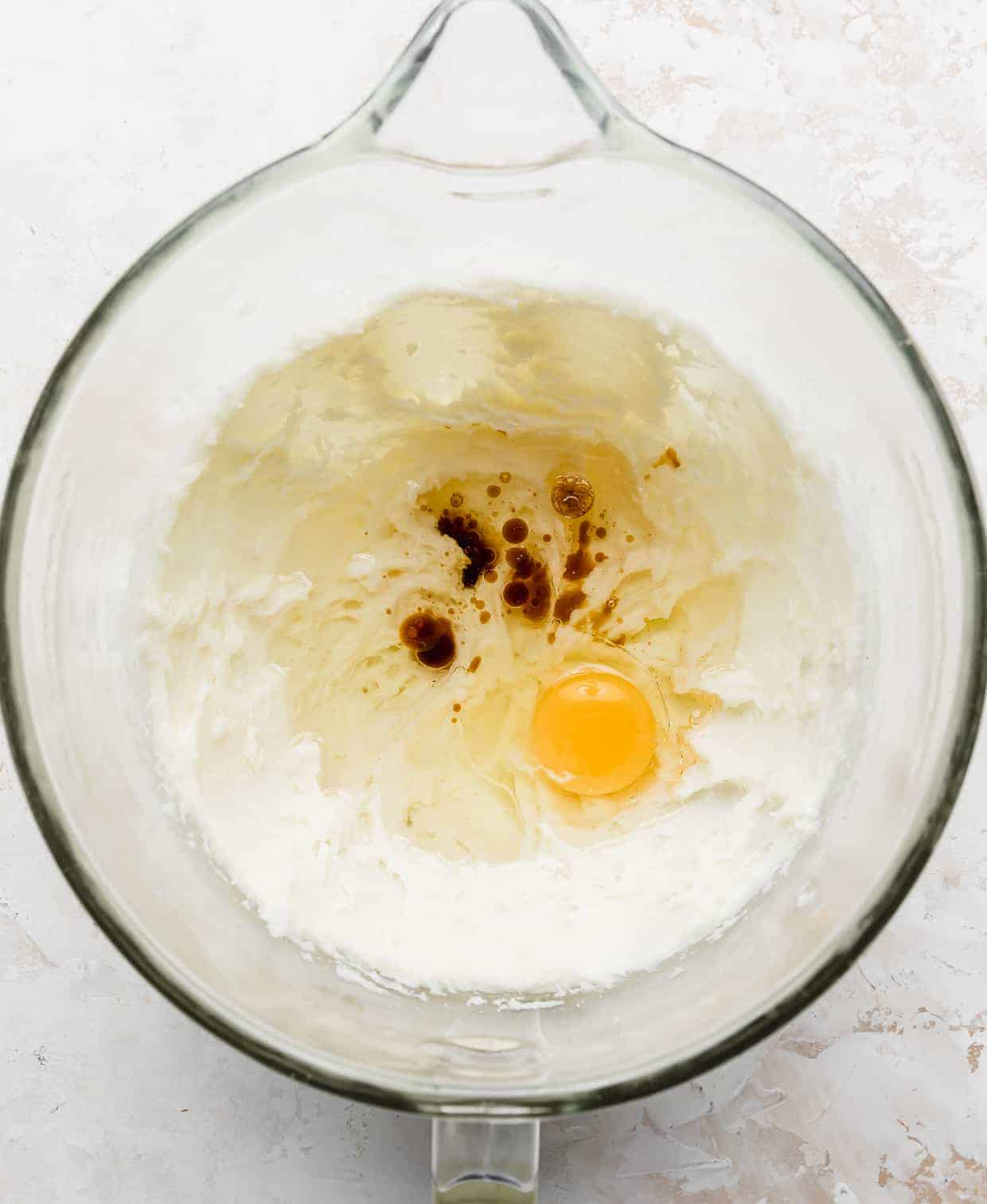 An egg, oil, and vanilla extract in the bowl of a stand mixer with creamed sugar and cream cheese.