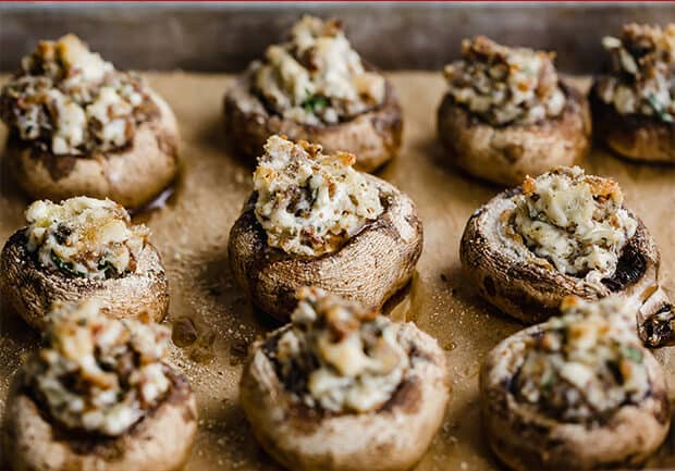 Mushrooms on a baking sheet stuffed with Italian sausage and topped with bread crumbs.
